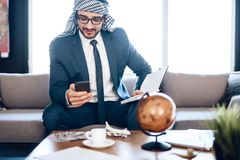 Arab businessman on phone with notebook on couch at hotel room. Bearded arab businessman in suit on phone with notebook on couch at office room royalty free stock photos