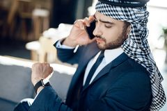 Arab businessman speaking on phone on couch at hotel. Bearded arab businessman in suit speaking on phone on couch at hotel Royalty Free Stock Photography