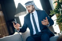 Arab businessman speaking on phone on couch at hotel. Bearded arab businessman in suit speaking on phone on couch at hotel Royalty Free Stock Images