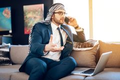 Arab businessman speaking on phone on couch at hotel room. Bearded arab businessman in suit speaking on phone on couch at hotel room Royalty Free Stock Photos