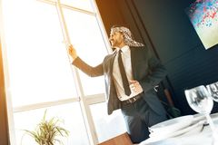 Arab businessman standing at window with model airplane. Stock Image