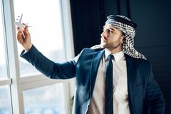 Arab businessman standing at window with model airplane. Stock Images
