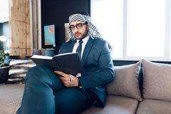Arab businessman taking notes on couch at office room. Bearded arab businessman in suit taking notes on couch at office room royalty free stock image