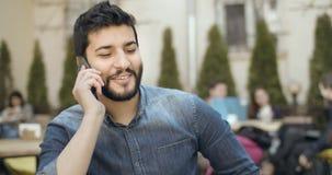 Talking on smartphone. Bearded arab man talking hapily on smartphone stock video
