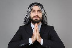 Bearded arabian muslim businessman in keffiyeh kafiya ring igal agal classic black suit shirt isolated on gray