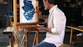 Bearded artist sitting in front of easel and painting. Abstract picture in studio stock footage