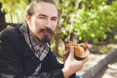 Bearded Asian man with hot dog, outdoor lunch Royalty Free Stock Images
