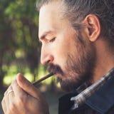 Bearded Asian man lights a cigar Stock Photography