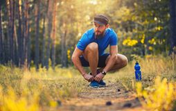 A bearded athlete ties up the shoelaces. A bearded athleteties up the shoelaces. healthy lifestyle concept royalty free stock images