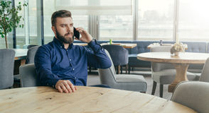 Bearded attractive businessman in blue shirt is sitting at wooden round table in restaurant and talking on cell phone. Royalty Free Stock Photos