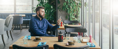 Bearded attractive businessman in blue shirt is sitting at wooden table near window in restaurant and holding smartphone Stock Photo