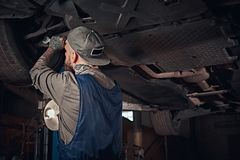 Bearded auto mechanic in a uniform repair the car`s suspension with a wrench while standing under lifting car in repair. Bearded auto mechanic in a uniform royalty free stock photography