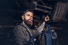 Bearded auto mechanic in a uniform repair the car`s suspension with a wrench while standing under lifting car in repair. Bearded auto mechanic in a uniform stock image