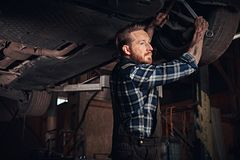 Bearded auto mechanic in a uniform repair the car`s suspension with a wrench while standing under lifting car in repair. Bearded auto mechanic in a uniform royalty free stock images