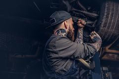 Bearded auto mechanic in a uniform repair the car`s suspension with a wrench while standing under lifting car in repair. Bearded auto mechanic in a uniform royalty free stock photos