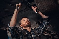 Bearded auto mechanic in a uniform repair the car`s suspension with a wrench while standing under lifting car in repair. Bearded auto mechanic in a uniform stock photography