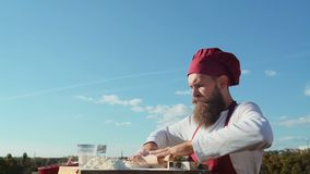 Bearded baker.Baker cooking outside. Eco bakery. Baker bake a fresh bread.  stock footage