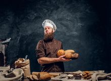 A bearded baker wearing a uniform holding fresh bread, standing next to a table, decorated with delicious bread loaves. Baguettes and muffins in a dark studio stock photography