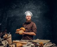 A bearded baker wearing a uniform holding fresh bread, standing next to a table, decorated with delicious bread loaves. Baguettes and muffins in a dark studio royalty free stock photography