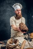 A bearded baker wearing a uniform showing fresh bread standing next to a table, decorated with delicious bread loaves. Baguettes in a dark studio. Vertical stock photos