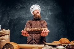 A bearded baker wearing a uniform showing fresh bread standing next to a table, decorated with delicious bread loaves. Baguettes and muffins in a dark studio stock photos