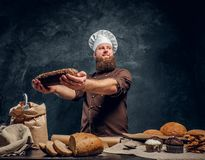 A bearded baker wearing a uniform showing fresh bread standing next to a table, decorated with delicious bread loaves. Baguettes and muffins in a dark studio stock photography
