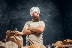 A bearded baker wearing a uniform standing with his arms crossed next to a table, decorated with delicious bread loaves. Baguettes and muffins in a dark studio stock image