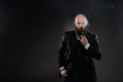 Bearded bald elegant man smoking a pipe Royalty Free Stock Photos