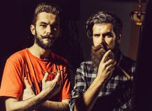 Bearded barber men with razor. Handsome bearded men hipster with stylish haircut, mustache and beard holding razor or shaver and scissors in checkered and orange royalty free stock photos
