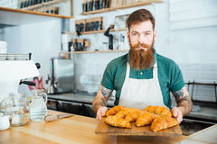 Bearded barista standing and holding wooden board with croissants. Attractive bearded barista standing in cafe and holding wooden board with croissants Royalty Free Stock Photography