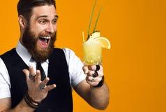 Bearded barman with beard holding cocktail in waistcoat stock image