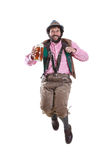 Bearded, bavarian guy jumping with wheat beer. Full body portrait of a middle-aged man in traditional, authentic bavarian dress, jumping with beer Royalty Free Stock Image