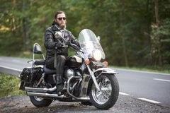 Bearded biker in black leather jacket on modern motorcycle on country roadside. Handsome bearded motorcyclist in black leather clothing and dark sunglasses stock photography