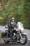 Bearded biker in black leather jacket on modern motorcycle on country roadside. Young bearded biker in black leather clothing and dark sunglasses sitting on royalty free stock images