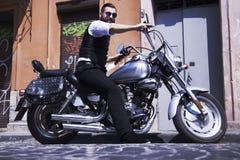 Bearded Biker Man in black jacket sitting on motorbike outdoors Stock Photo