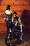 Bearded biker man on motorbike. Pretty cute women or girl near young handsome bearded men hipster or biker with long beard sitting on metallized motorbike or royalty free stock photos