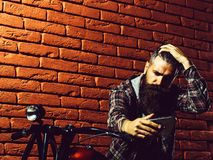 Bearded biker man on motorbike. Young handsome bearded man hipster or biker with long beard sitting on metallized motorbike or motor cycle on red brick wall stock images