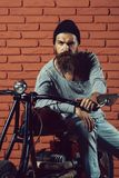 Bearded biker man on motorbike. Young handsome bearded man hipster or biker with long beard sitting on metallized motorbike or motor cycle on red brick wall stock photo