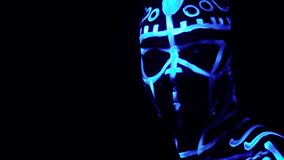 A bearded black man in neon patterns under ultraviolet light looks into the camera standing in the dark, slow motion