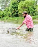 Bearded brutal fisher catching trout fish with net. Fishing is an astonishing accessible recreational outdoor sport