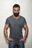 Bearded brutal guy wearing blank grey t-shirt Royalty Free Stock Photography