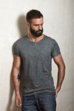 Bearded brutal guy wearing grey t-shirt Royalty Free Stock Photo