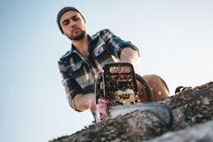 Bearded brutal lumberjack wearing plaid shirt sawing tree with chainsaw for work on sawmill. Wooden sawdust fly apart royalty free stock image
