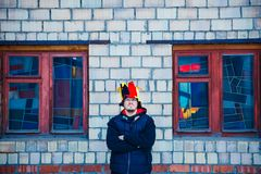 Bearded brutal man in the hat of a buffoon stands near the brick wall. And color windows stock images