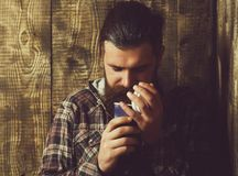 Bearded brutal man opening blue plastic cup. Bearded brutal man or caucasian hipster with long beard and moustache in fashionable plaid jacket opening blue royalty free stock photo