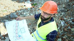 Bearded builder engineer analyzes the drawing of the building, on the background of the bricks of the destroyed building. Preparation for construction stock footage