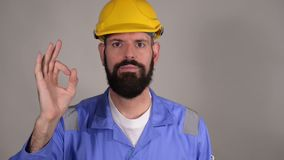 Bearded builder in helmet showing ok gesture ,concept of success and approval over grey background. Bearded builder in hard hat showing ok gesture ,concept of stock video
