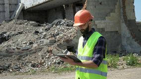 Bearded builder in a helmet and reflective vest uses a tablet on the background of a destroyed building, preparing for. Demolition and construction stock video footage