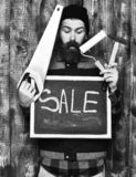 Bearded builder holding various building tools and board, surprised face. Bearded builder man, long beard, brutal caucasian hipster with moustache holding royalty free stock photography
