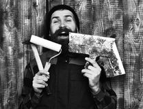 Bearded builder man holding various building tools with happy face. Bearded builder man, long beard, brutal caucasian hipster with moustache in uniform holding stock photos